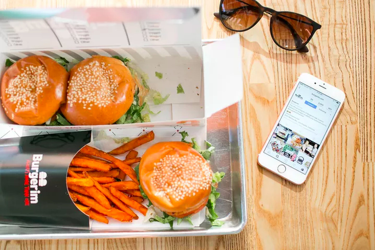 three sliders with orange-colored fries on a table with sunglasses and a cellphone