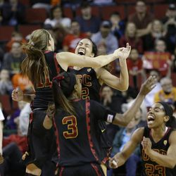 Southern California players rush to congratulate each other after beating Oregon State in the Pac-12 NCAA college championship basketball game Sunday, March 9, 2014, in Seattle.  USC won 71-62. (AP Photo/Elaine Thompson)