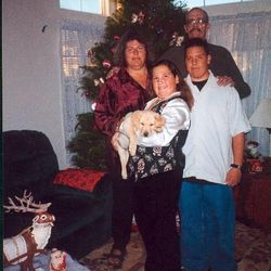 Sarah Robles, front, holds the family dog at Christmas time. From left is her mother, Joy, father, Dennis, and brother, Glen.