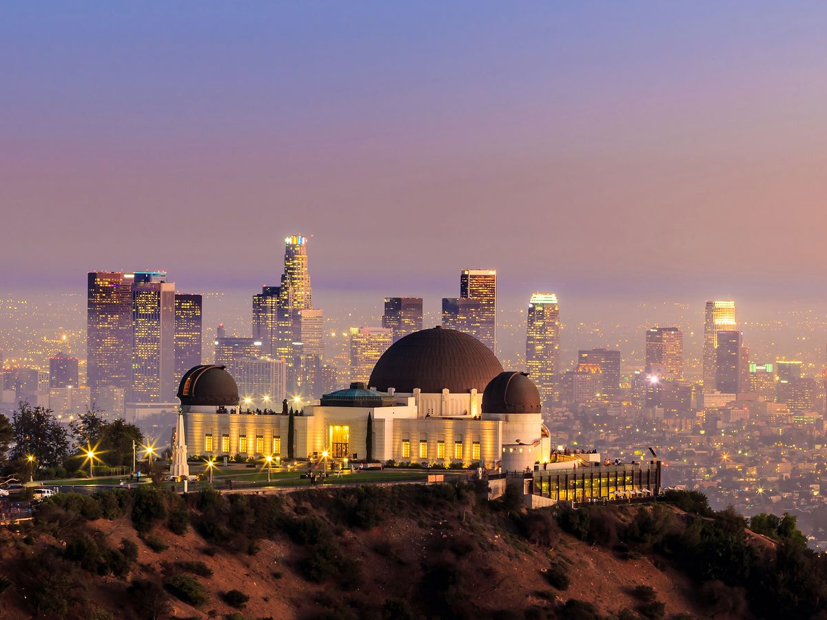 The exterior of the Griffith Observatory. The facade is white and there are multiple brown domes. The observatory is on a cliff. The city of Los Angeles is in the distance.