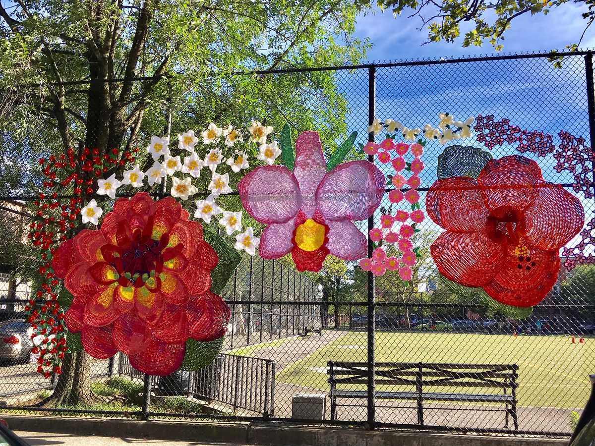 A group of crocheted flowers attached to a gate that surrounds a field, in East Harlem.