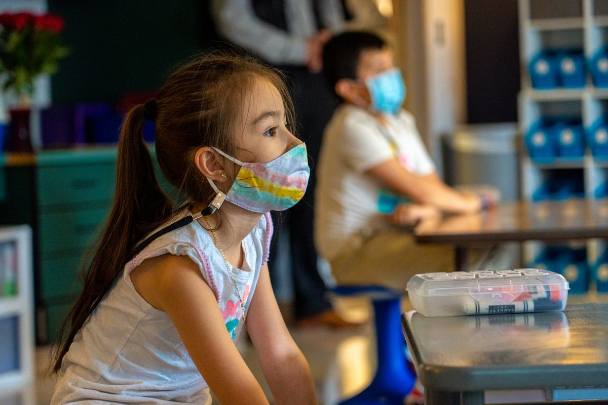 Girl with a mask sits in class
