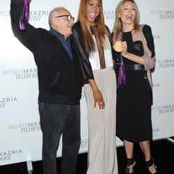 Olympic gold medalist Sanya Richards-Ross, center, shows her medals to designers Max, left, and Lubov Azria  before the BCBG MAX AZRIA Spring 2013 collection is shown at Fashion Week in New York, Thursday, Sept. 6, 2012.