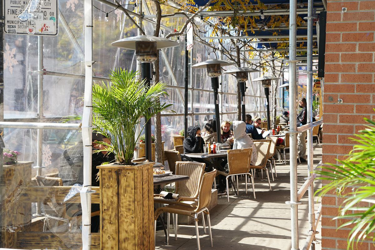 An outdoor dining area with heaters and people sitting at tables that's covered.