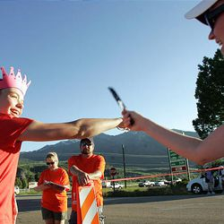Haily Hadfield receives the wristband from her teammate Mindy Chase, left, at the exchange point in Mountain Green during the Ragnar Relay Wasatch Back race Friday.