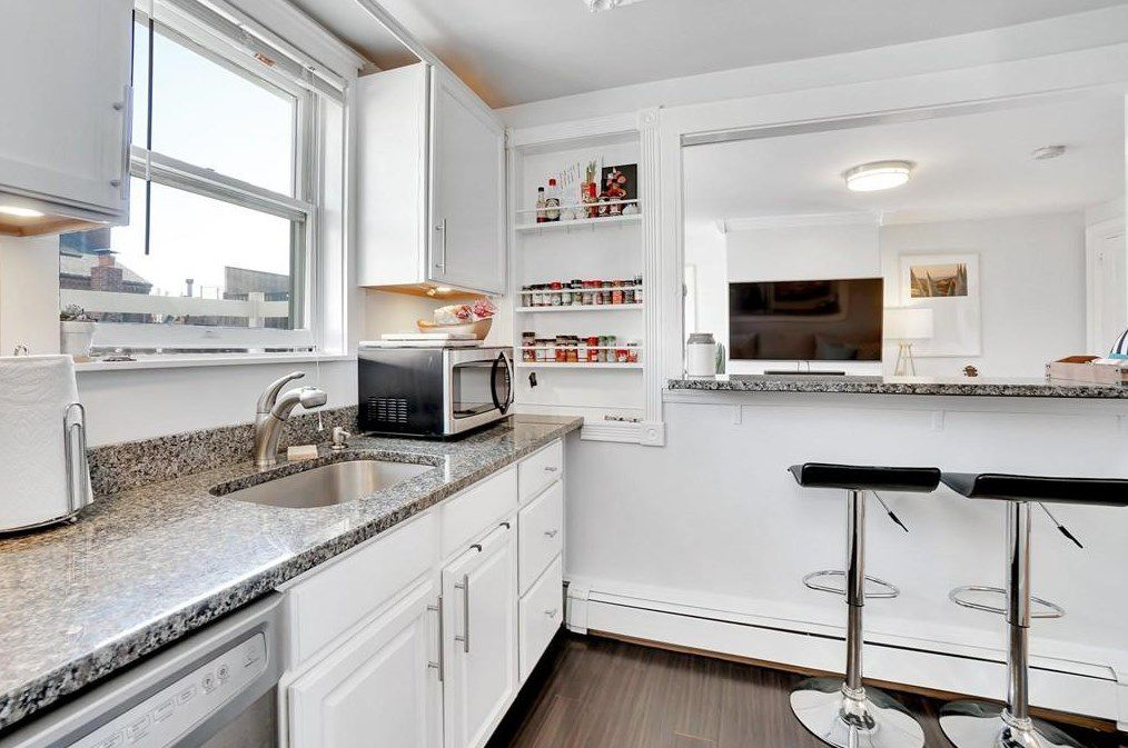 A kitchen with a run of countertop leading to a counter with two stools.