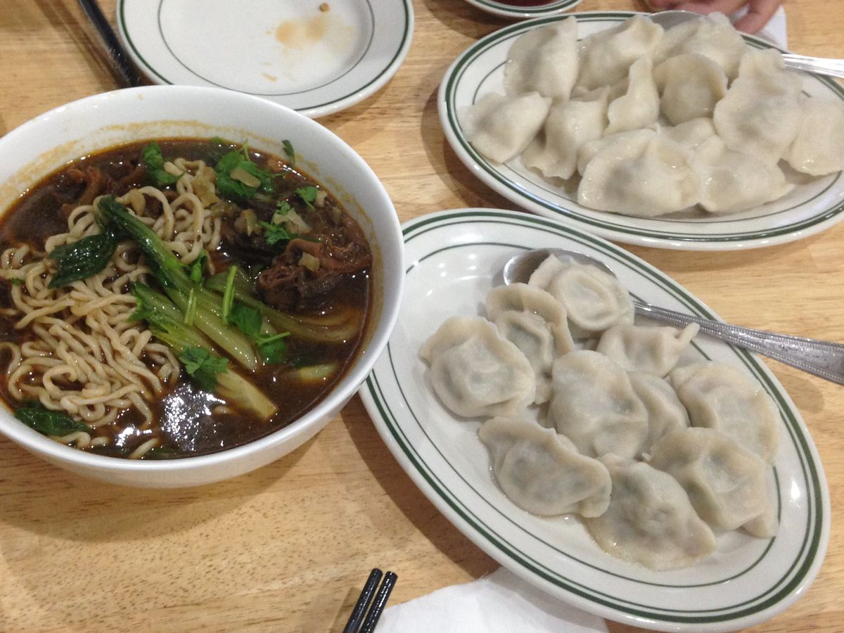 A spread of dumplings and beef noodle soup at New Dumpling