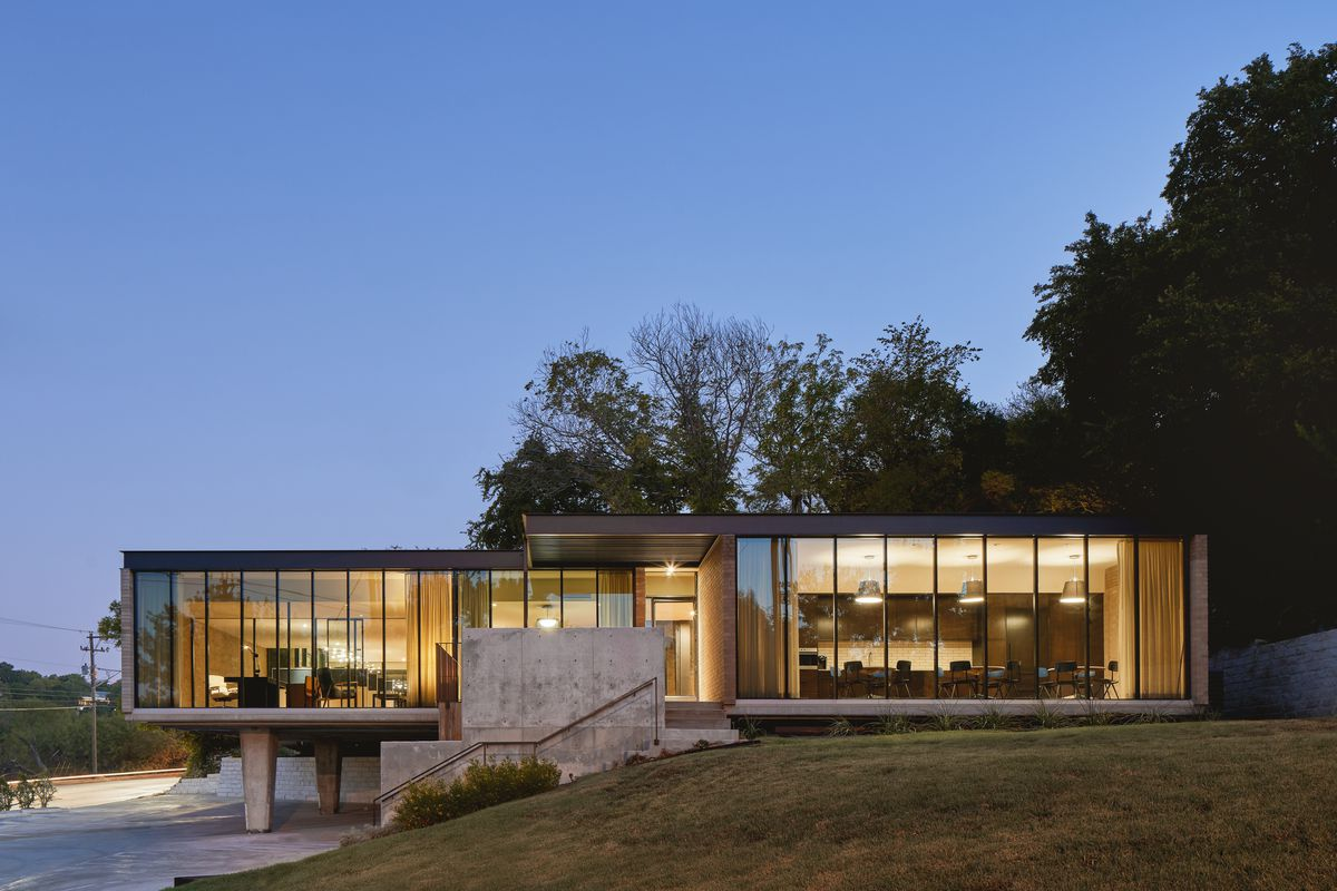 Photo of an midcentury office building at dusk. It's made up of two connected, horizontal, one-story brick structures with walls of windows on both longest sides. The structure closes to the road is cantilevered over a driveway. There is a tapered concrete post under that part of the building.