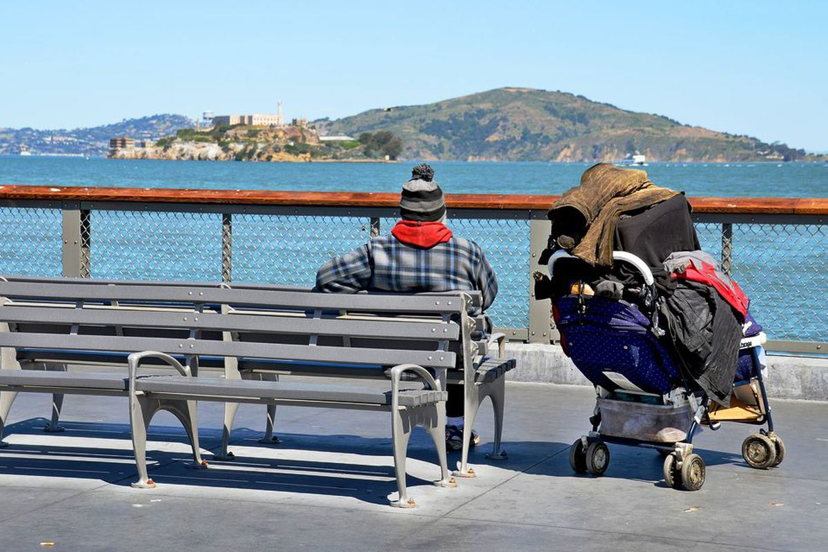 An apparently homeless man sitting on a bench and looking at the bay.