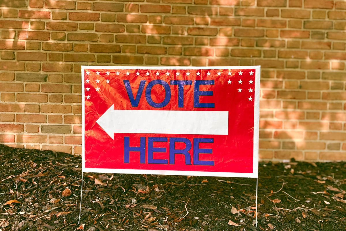 A red sign reads Vote Here.
