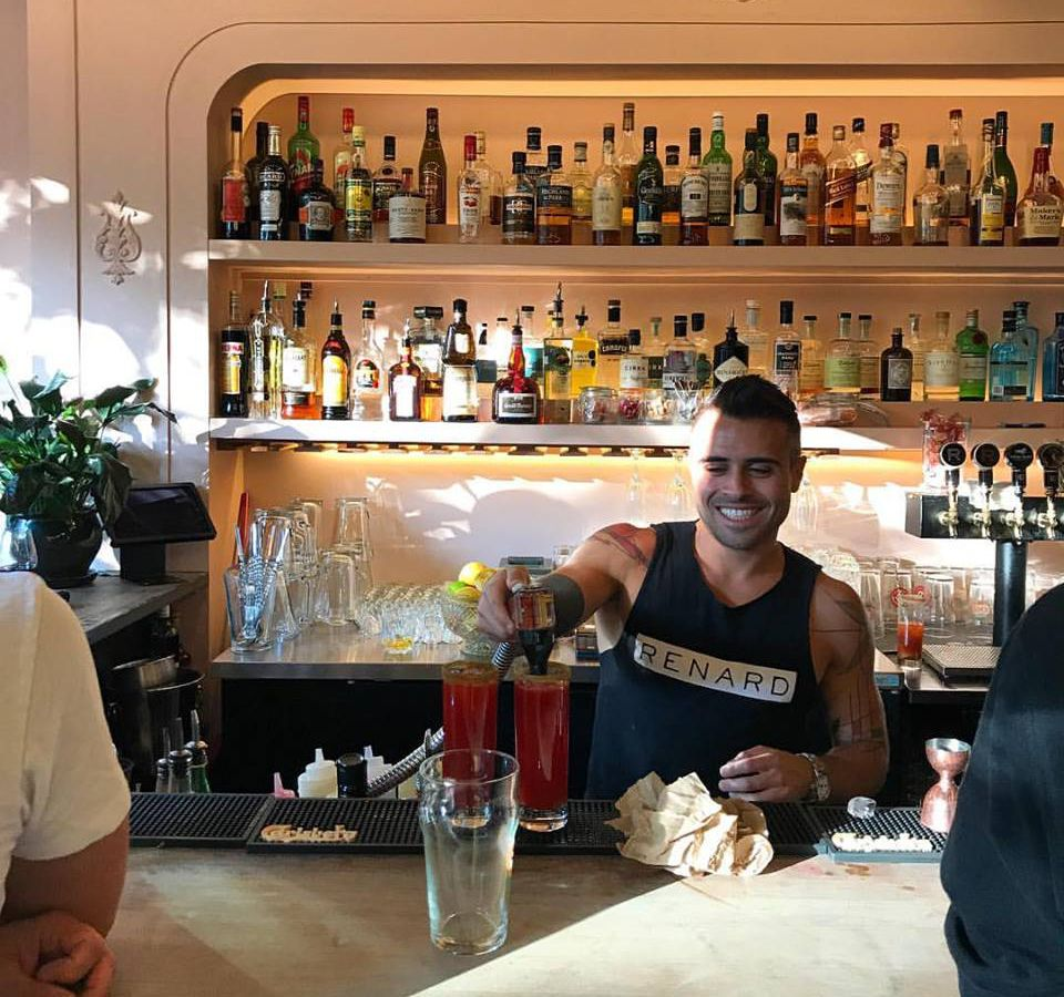 A bartender in a tank top pours drinks in front of a wall of liquor bottles.