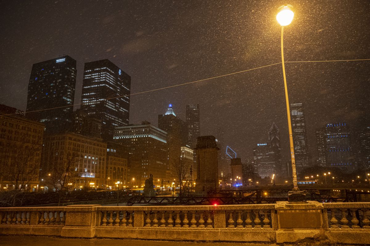 Snow falls on the city of Chicago near the Congress Triangle Garden in the Loop, Monday, Jan. 25, 2021.