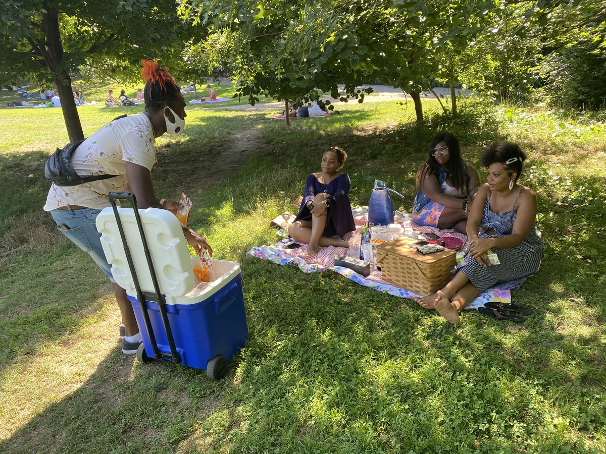 A man in a mask is bending down to sell drinks to three women sitting on a mat in a park