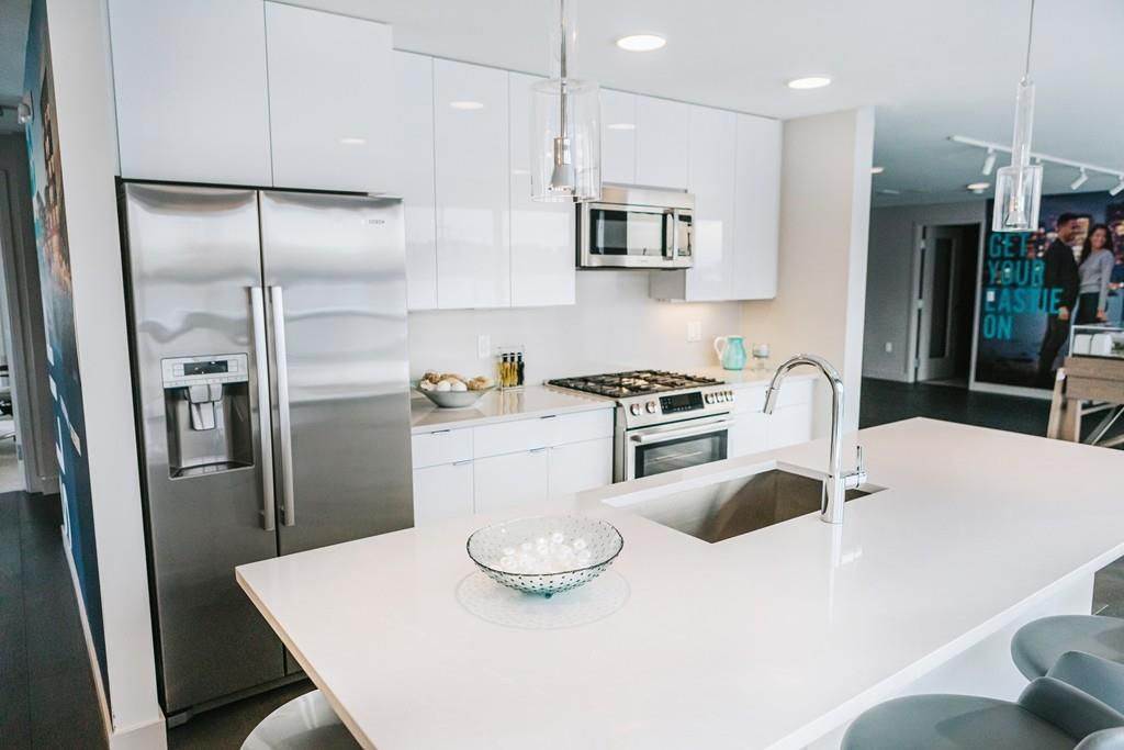 A new, modern kitchen with a large island in the forefront.