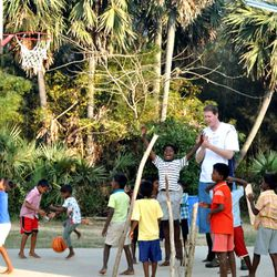 Shawn Bradley plays basketball with children at the Rising Star Outreach campus in Thottanaval, India.