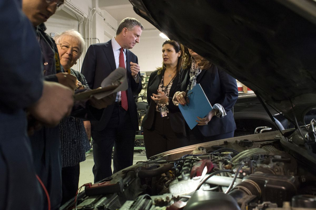 Mayor Bill de Blasio spoke in 2015 with Automotive High School Principal Caterina Lafergola, who later left the school. Automotive is one of eight schools where teachers have had to reapply for their jobs in recent years.Now, teachers at two more schools will have to do the same. (Ed Reed/Mayoral Photography Office)