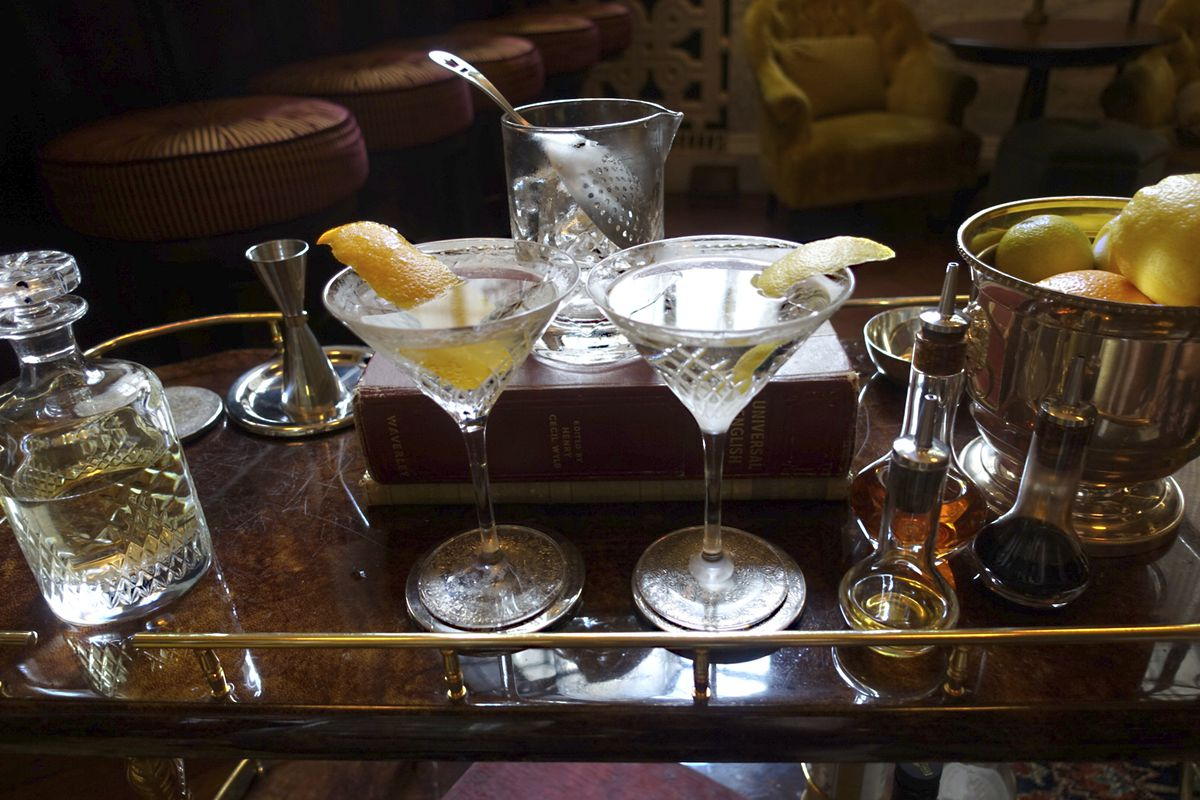 A picture of a Star of Bombay Martini, left, at the Library Bar at the Ned hotel in London, Wednesday, June 19, 2019. The martini's heyday began almost a century ago, but today's bartenders have some innovative takes on the classic cocktail. (AP Photo/Sia