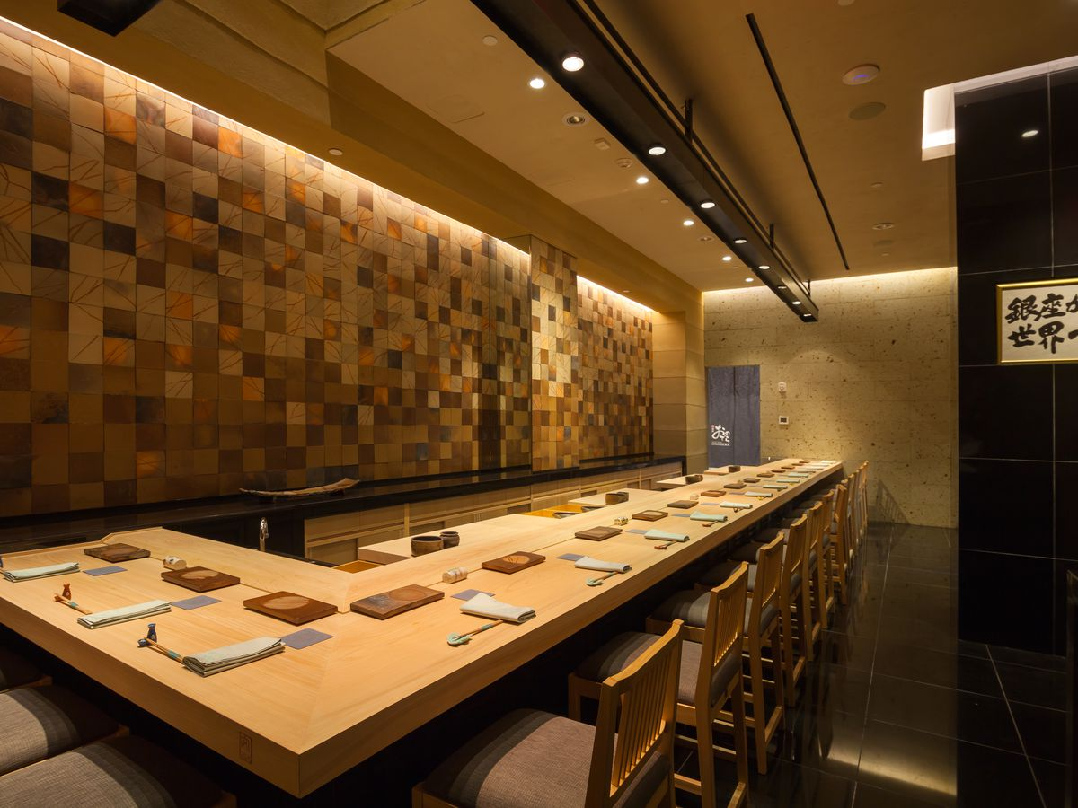 A lengthy corner sushi counter, with napkins and utensils set for service. In the background, one wall is composed of checkered light and dark woods.