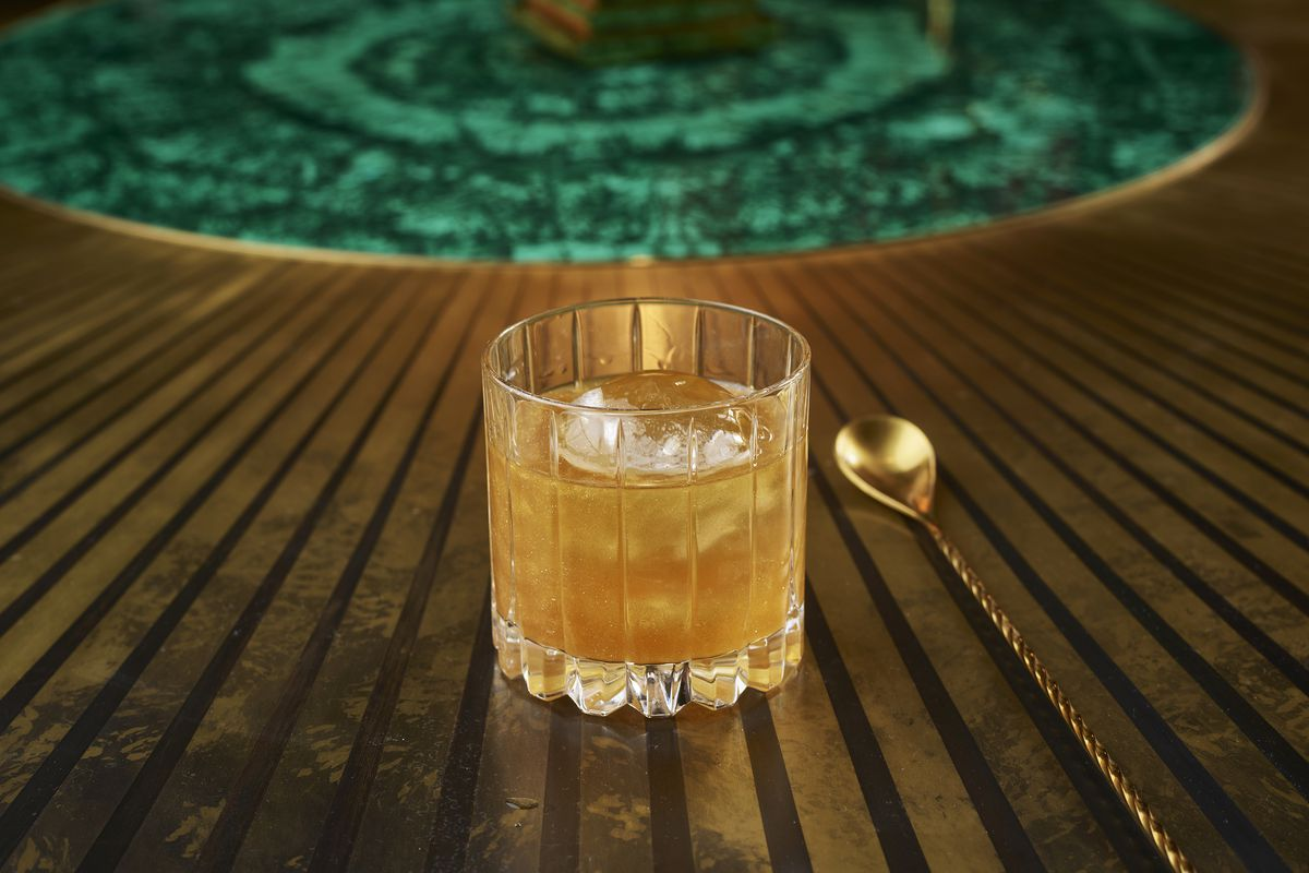 A golden cocktail on a dark wood surface