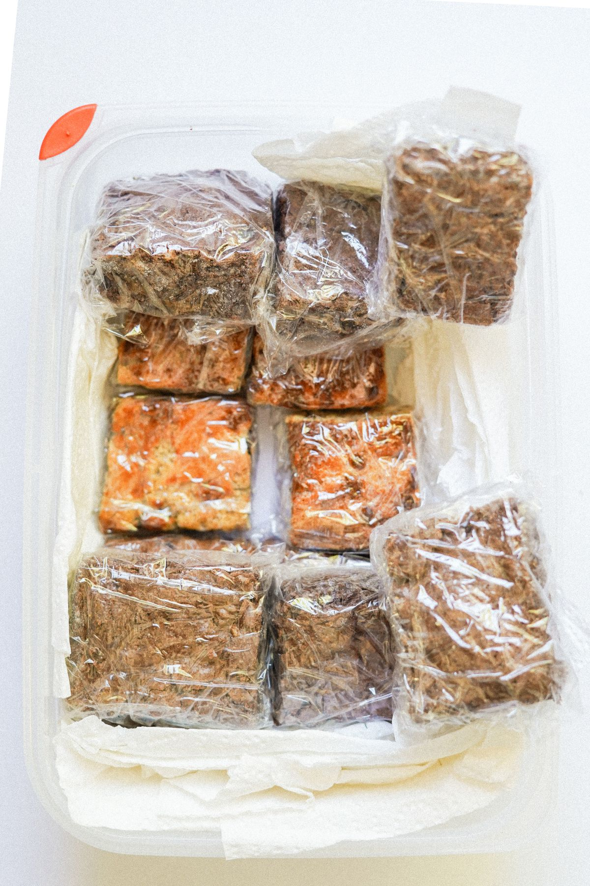 Brownies and blondies cut into squares and wrapped in plastic wrap, packed in a clear Tupperware.