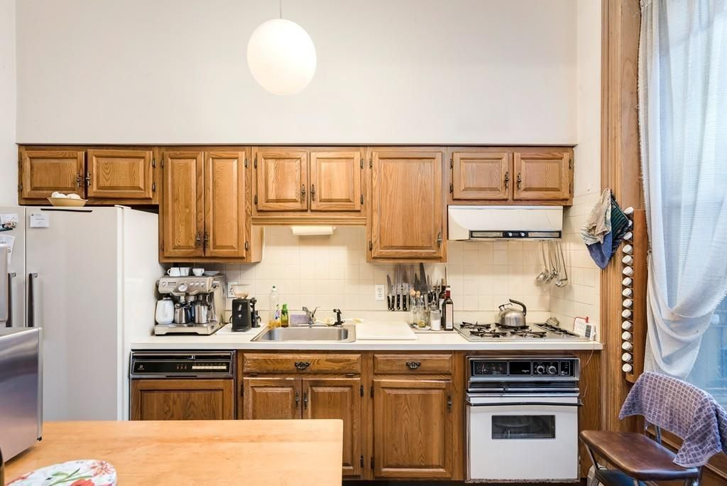 An older, but spacious kitchen with a long counter.