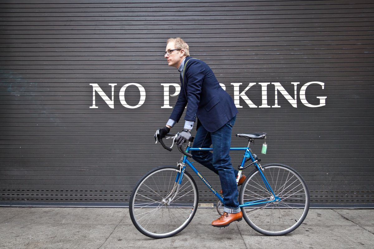 A man on a blue bicycle. The man is wearing a blue blazer and denim jeans. He has leather gloves on his hands. In the background is a black gate with the words: No Parking.