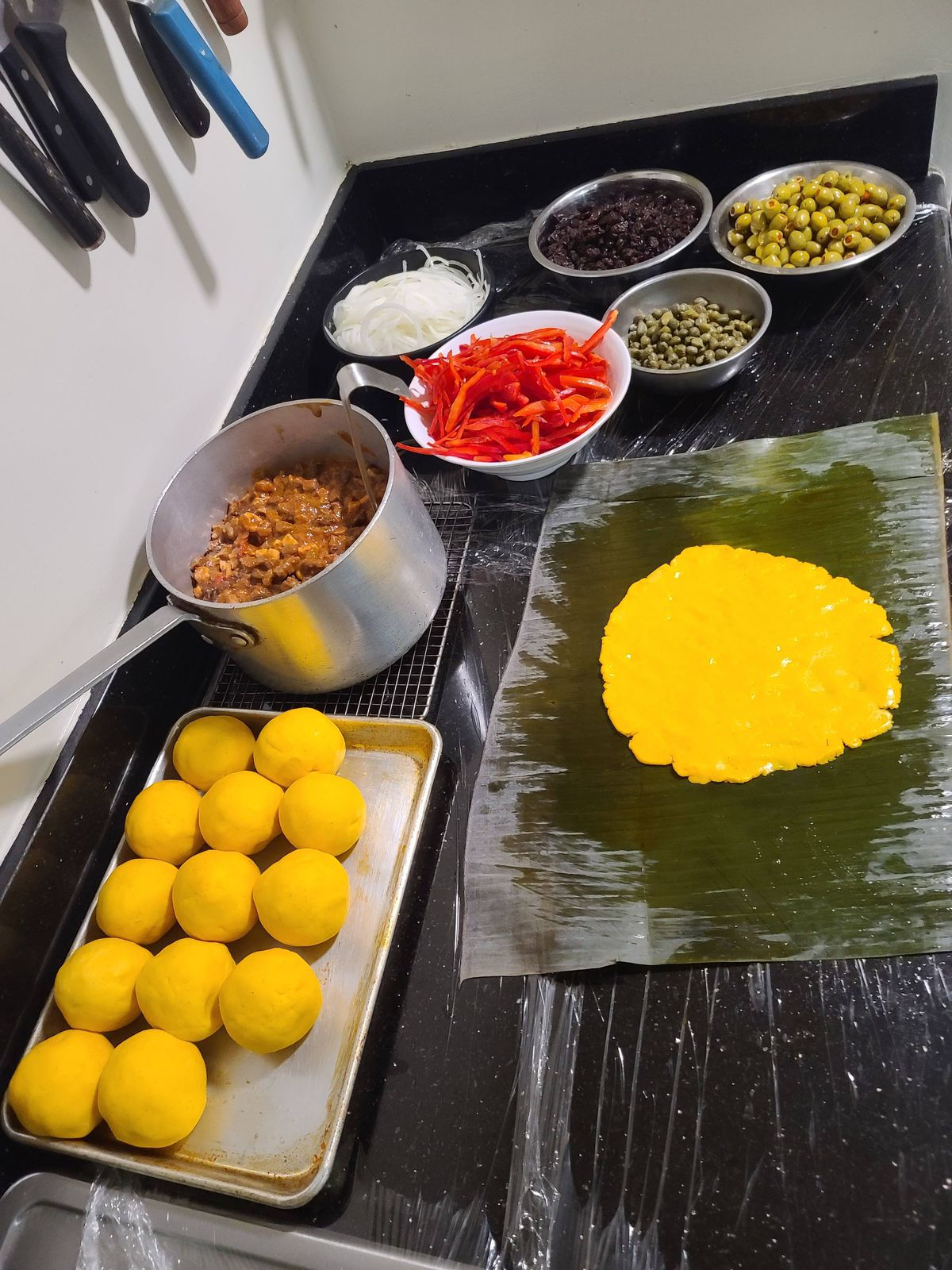 Ingredients for making hallaca: balls of raw corn dough, a meat stew, peppers, olives, and raisins