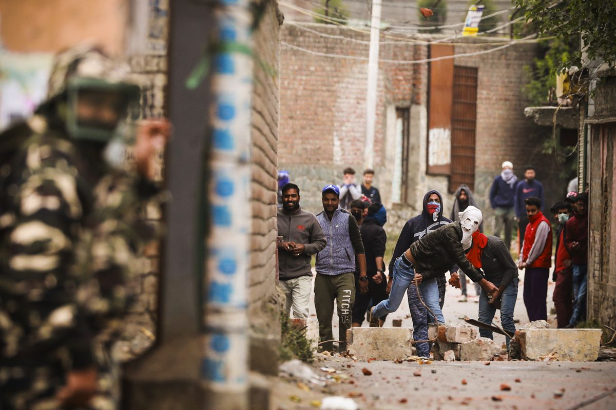 Protesters hurl stones towards police and paramilitary men during clashes on the outskirts of Srinagar, India, on October 16, 2018.