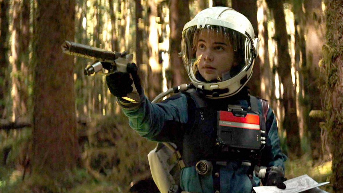 Sophie Thatcher, a young woman in handmade-looking space gear, points a handmade-looking gun offscreen in Prospect