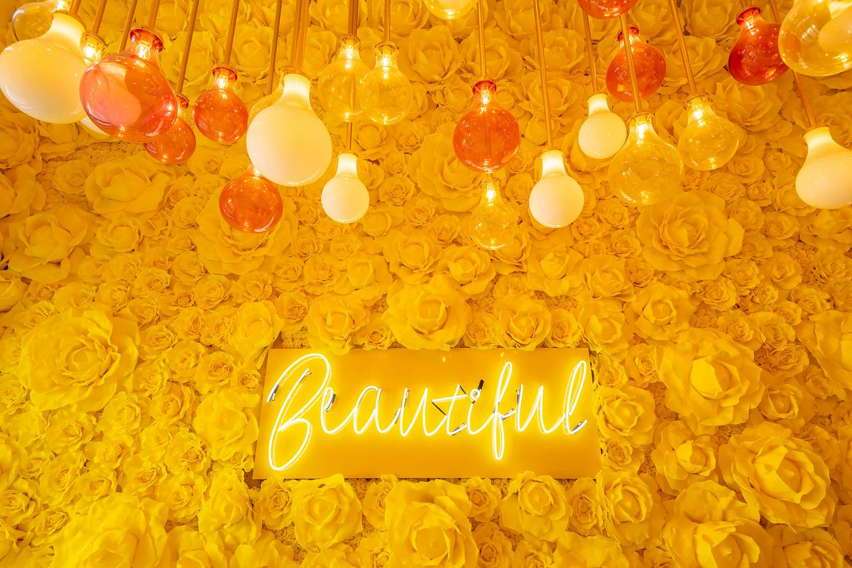 A bright yellow flower wall at the new Sugar Factory at Westfield Century City.