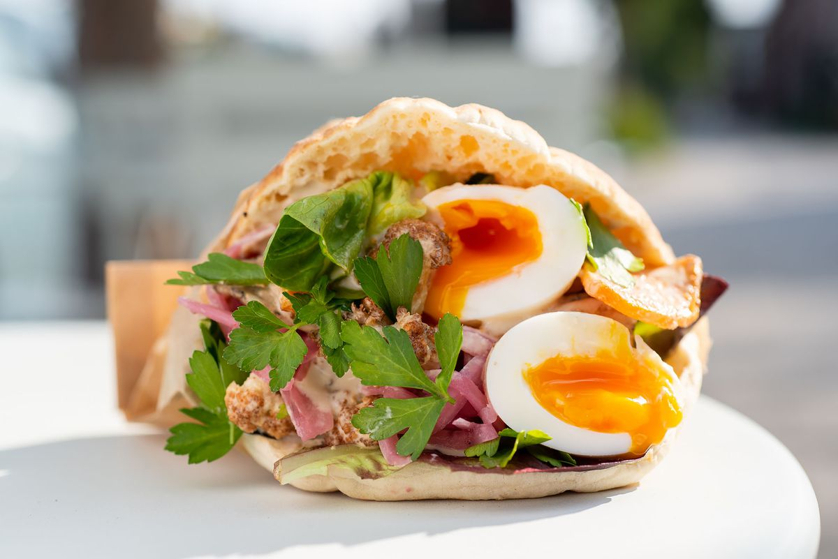Jammy eggs and greens inside a pita sandwich in the sun.