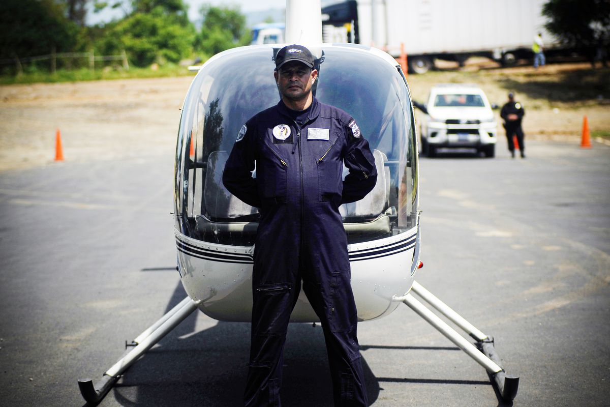 A migration officer stands in front of a helicopter.