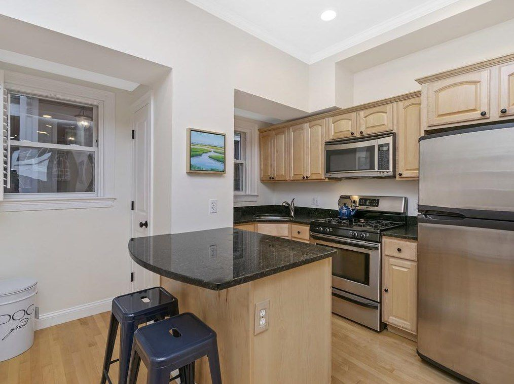 That open kitchen with an island and two chairs in front.