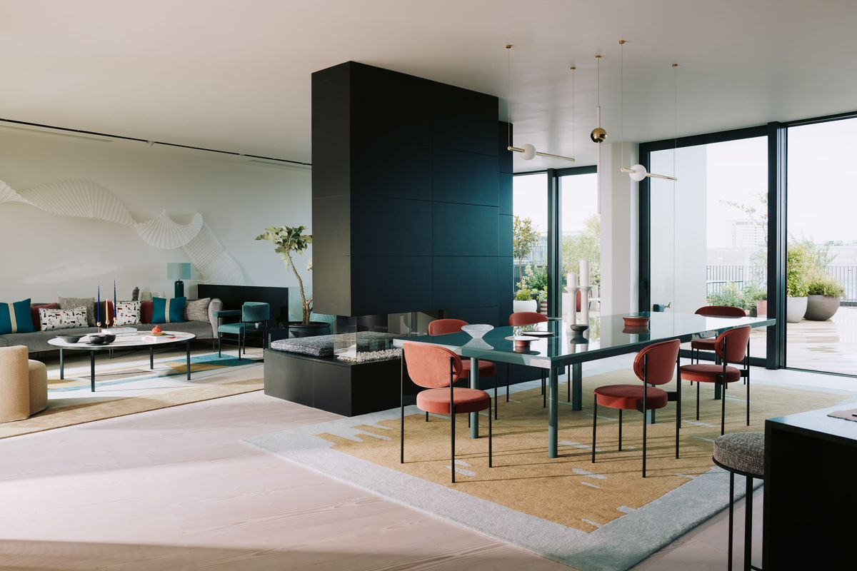 Open living and dining room with a black fireplace module in the center and glass walls in the distance.