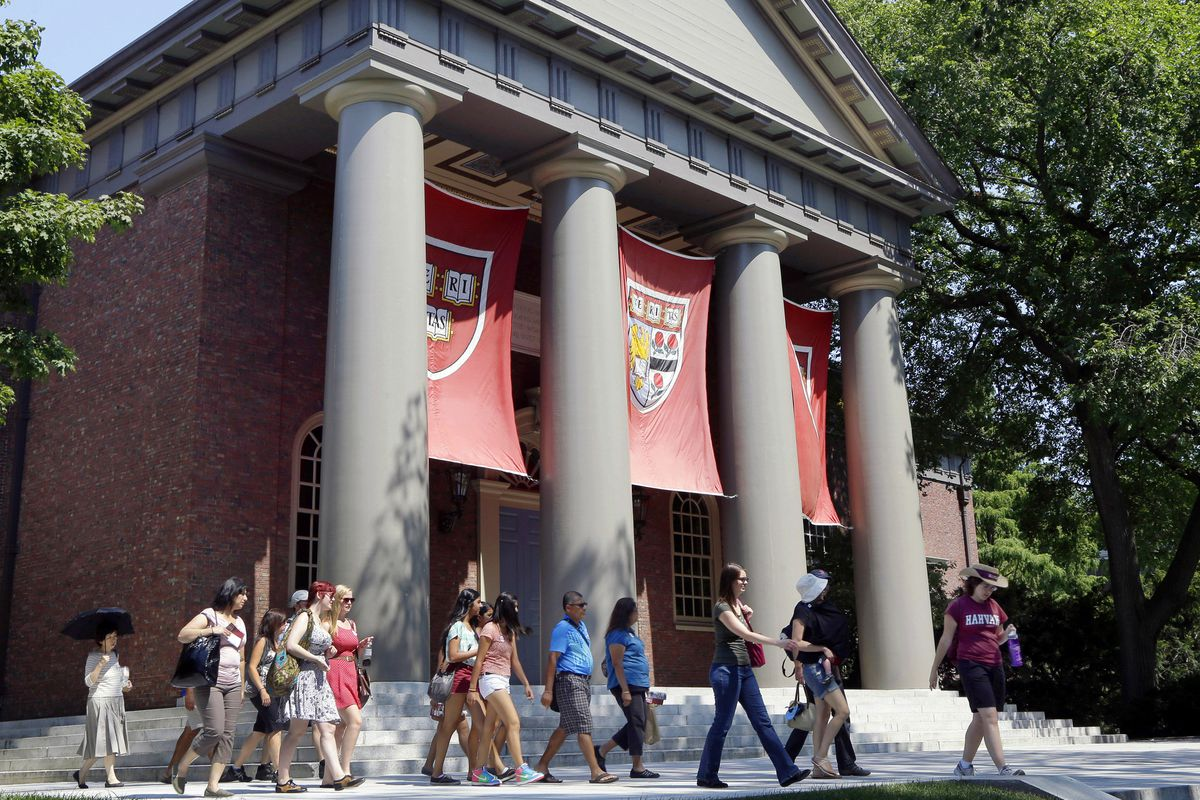 FILE - In this Aug. 30, 2012, file photo, a tour group walks through the campus of Harvard University in Cambridge, Mass. The Justice Department has sided with Asian-American students suing Harvard University over the Ivy League school's consideration of