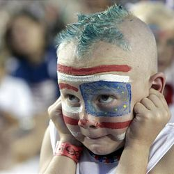 Seven-year-old Chase Gardner plugs his ears to muffle the loud music and fireworks during the 2009 Stadium of Fire at LaVell Edwards Stadium in Provo on Saturday.