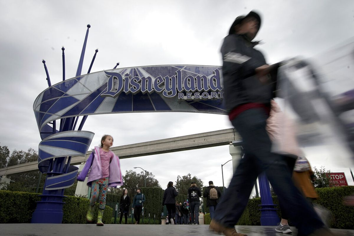 In this March 12, 2020, file photo, visitors to Disneyland make their way in and out of the parks in Anaheim, Calif. Disneyland has revealed new ticket prices and they're not a huge climb from before