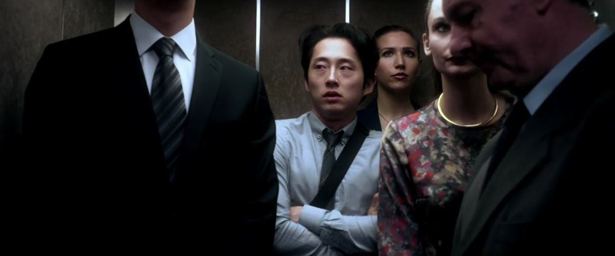 A still from Mayhem showing Steven Yeun in a crowded elevator