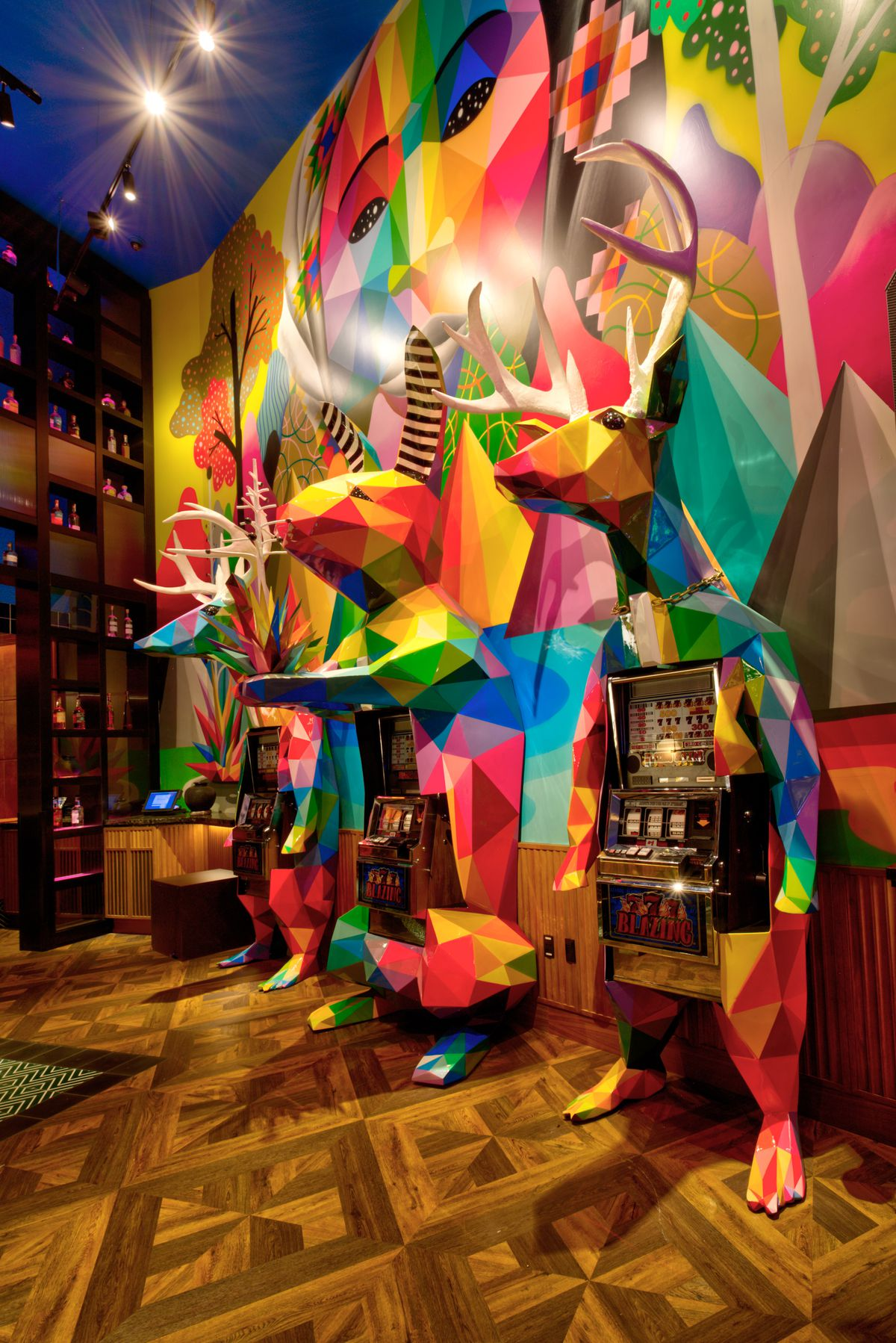 A colorful mural overlooks three slot machines