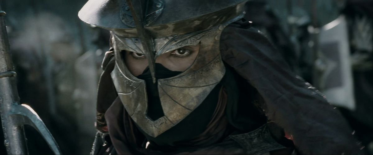 An Easterling soldier, with face-covering, khol-rimmed eyes, and a helm adorned with flowing foreign script in The Two Towers.