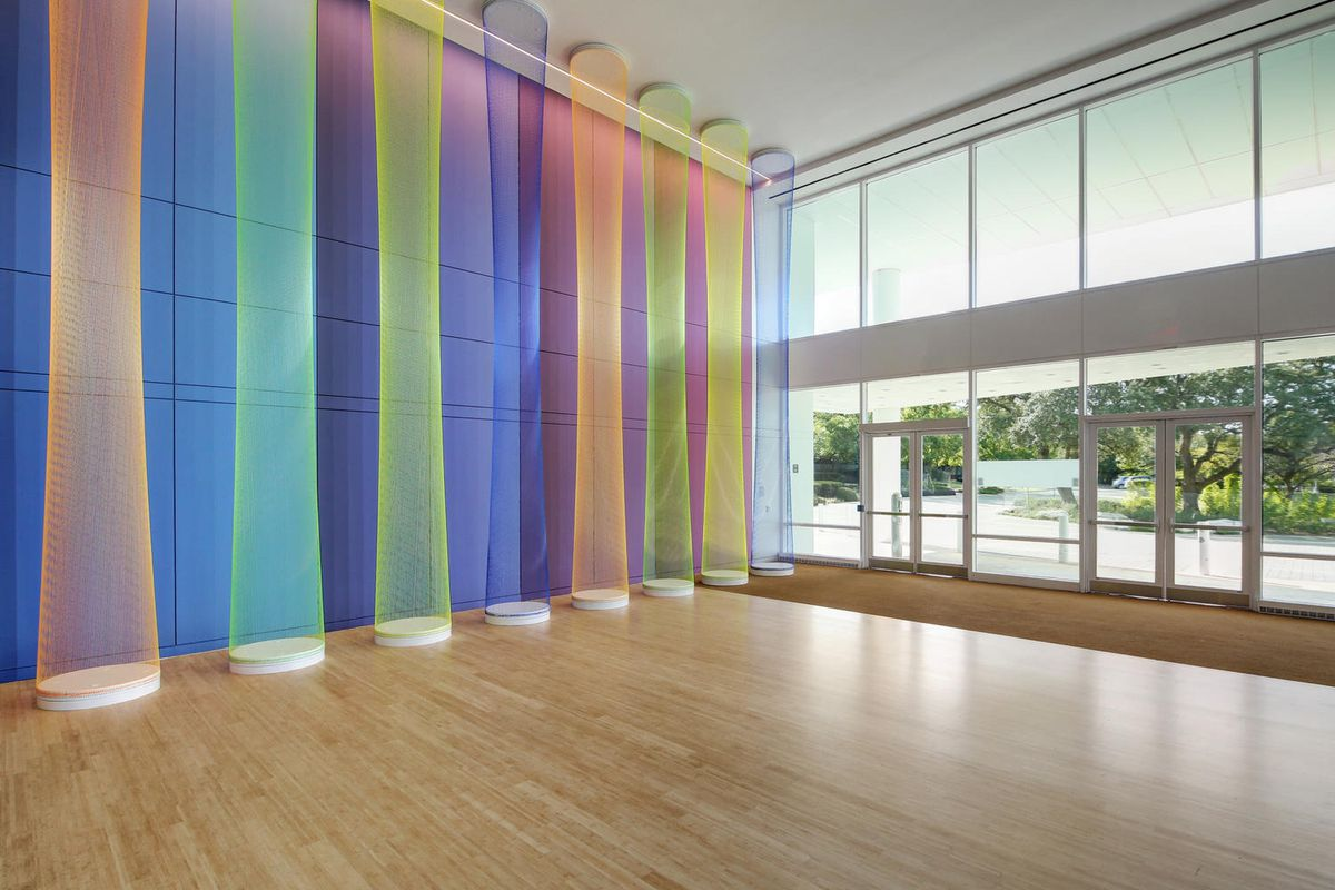 Tall sculptural light and painting in two-story building lobby