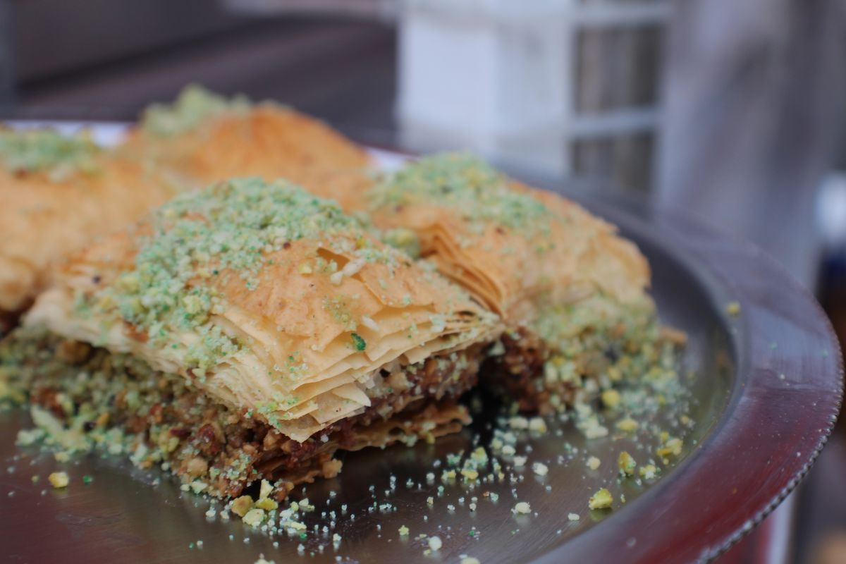 A closeup of flaky baklava, topped with chopped pistachios