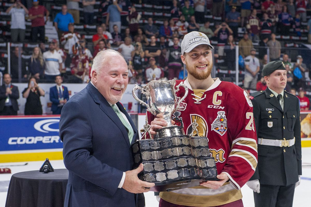 REGINA, SK - MAY 27: CHL president David Branch presents the 2018 Memorial Cup trophy to Jeffrey Truchon-Viel #25 of Acadie-Bathurst Titan after the win over Regina Pats at Brandt Centre - Evraz Place on May 27, 2018 in Regina, Canada.