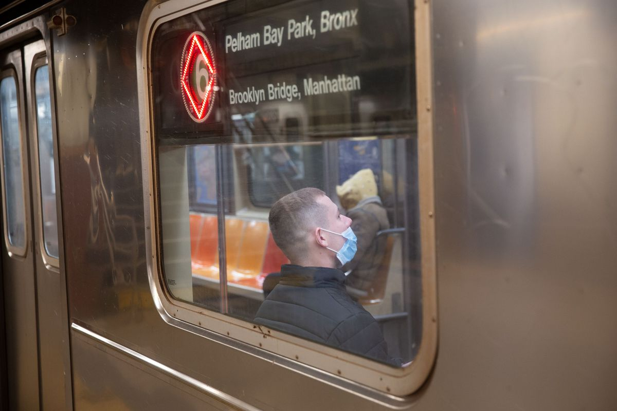 Riders wait for a 6 train to leave the City Hall station during the coronavirus epidemic.