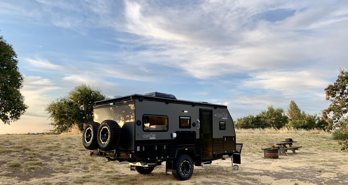 The gray and black trailer sits in a camping field with a picnic table, fire pit, and blue skies above.
