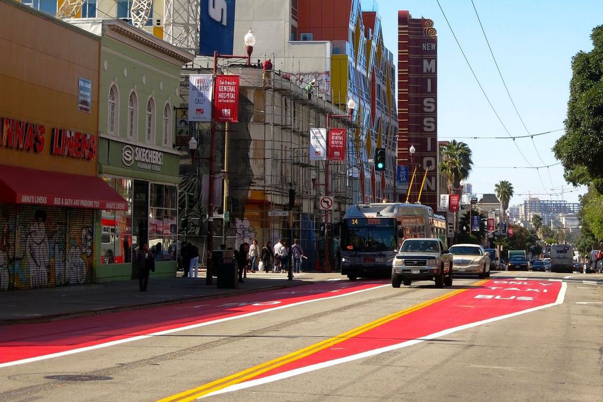 Cars and a Muni bus on Mission Street, with red traffic lanes.