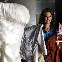 Julie Caldwell, 39, holds her former bridesmaid dresses as her wedding dress is shown in the foreground at her home, June 17, 2010 in Ennis, Texas.