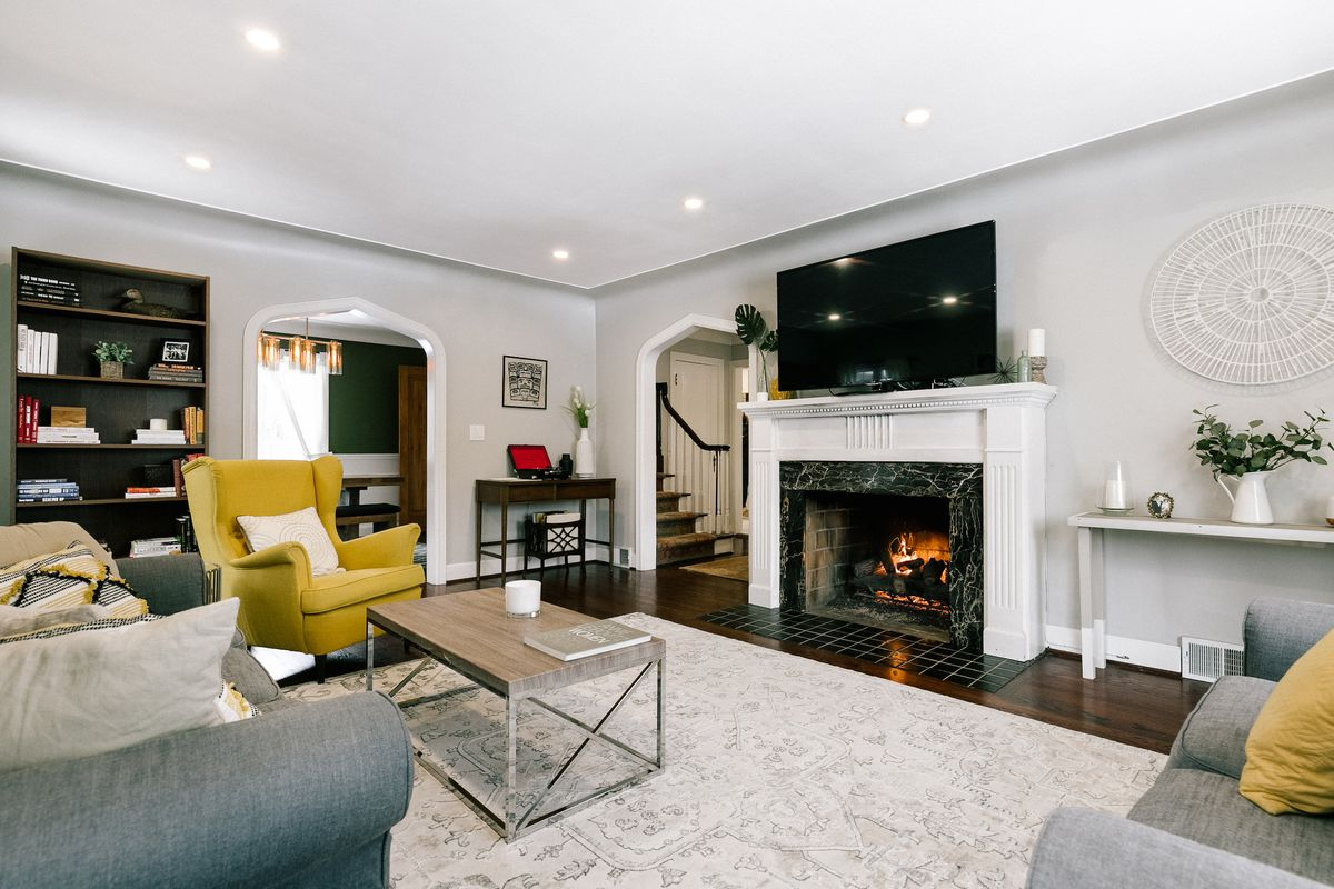 Living room with black marble fireplace and white wood mantel. There's a gray couch, yellow chair, and wood/glass coffee table on top of a mostly white carpet.