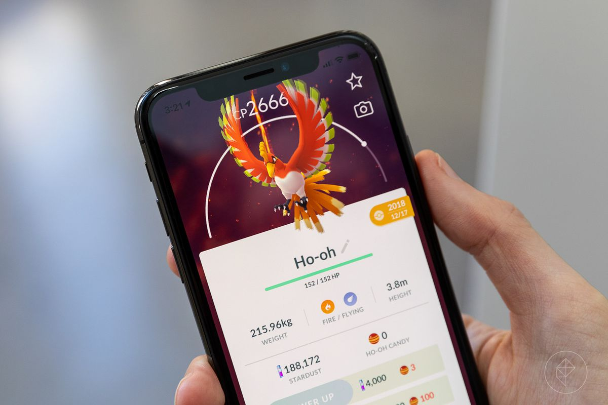 A hand holds up a phone with a Ho-oh's stat screen