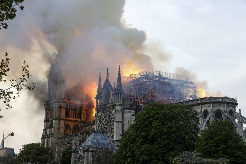 Flames and smoke are seen billowing from the roof of the Notre Dame Cathedral.